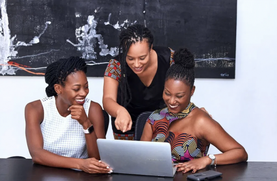 decorative photo: three smiling Black women interacting at a single laptop