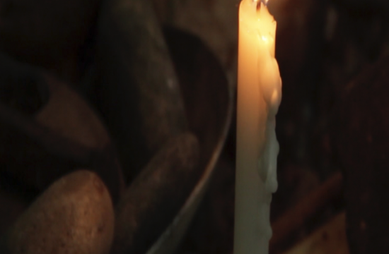 photo of a candle flame shedding dim light on a bowl of potatoes
