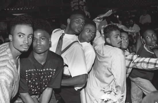 Black and white photo depicting a small crowd of Black LGBTQ people at a Ball, circa 1990